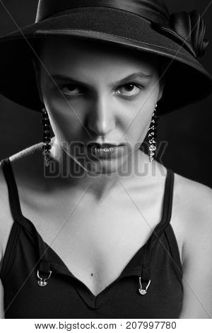 beautiful sad young woman in hat on black background, monochrome
