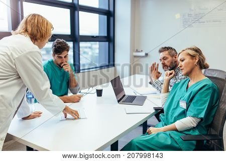Group of medical professionals brainstorming in a meeting. Team of healthcare workers discussing in boardroom with female doctor presenting her plan.