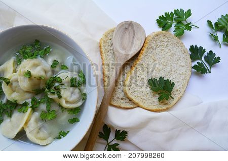 dumplings,  plate of dumplings in broth and herbs on the table