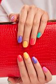 Multicolored nails and red leather handbag. Hands with beautiful summer manicure holding red lacquered handbag close up. Woman beauty and style. poster