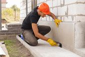 worker applies bitumen mastic on the foundation poster