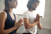Group of young sporty people making namaste gesture, man and woman meditating, practicing yoga lesson with instructor, working out, indoor close up image, studio. Wellbeing and wellness concept poster