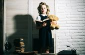 Child with briefcase and typewriter on table. Education and childhood. Kid choose career of journalist or writer. Little baby secretary in cabinet with bear. Small girl with curler in hair read book. poster