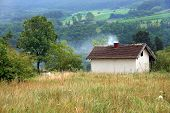 rural landscape of Serbia lonely house on yellow meadow with smoke from chimney poster