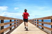 Running runner sport man jogging on beach boardwalk living active lifestyle. Workout outside person with fit body training for weight loss success, man taking step towards life happiness. poster