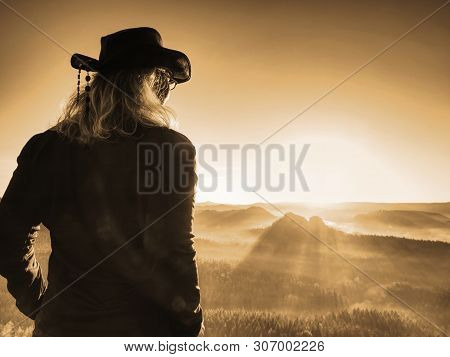 Beautiful Long Blond Hair Woman Wearing Cowgirl Hat And Dark Trekking Clothes  While Resting In Sunl