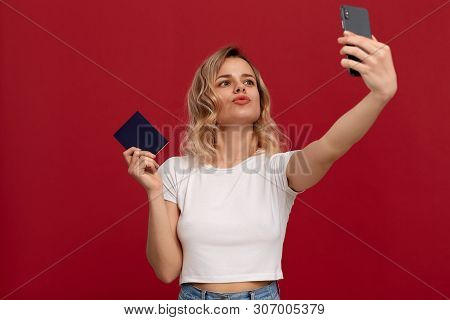 Portrait Of A Girl With Curly Blond Hair In A White T-shirt On A Red Background. Happy Model Makes S