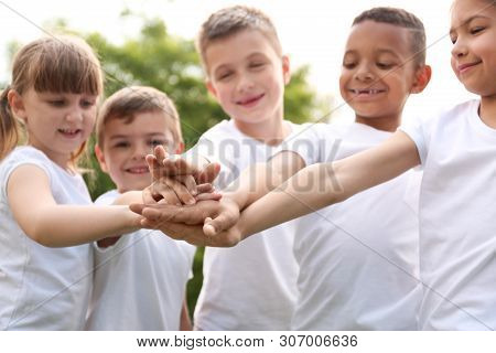 Group Of Kids Joining Hands In Park. Volunteer Project
