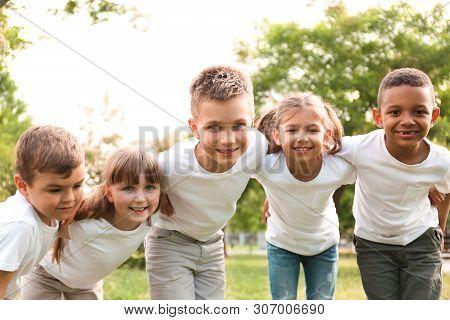 Group Of Children Huddling In Park. Volunteer Project