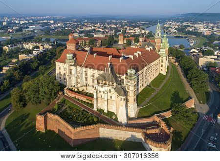Historic royal Wawel castle and cathedral in Cracow, Poland.  Aerial view in sunrise light early in the morning. Vistula River with Debnicki Bridge in the background poster
