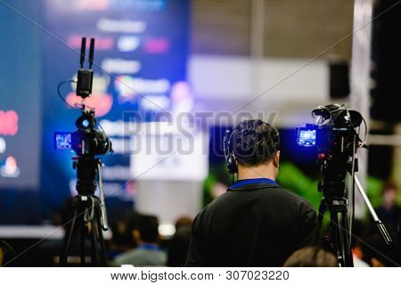 Selective Focus To Cameraman And Video Camera Set Are Recording To Speaker And Audience