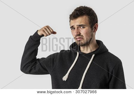 Weak Caucasian Young Man Is Looking Into The Camera Disappointedly. Isolated On White Background. We
