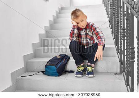 Front View Of Sad Blond Boy Sitting On Stairs In Corridor Of School And Leaning Head By Hand. Little