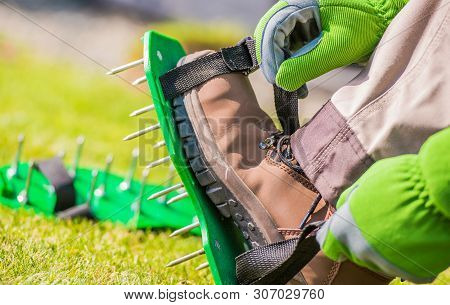 Spiked Aerator Shoes. Men Aerating His Lawn Strapping On These Spiked Shoes And Taking A Stroll Acro