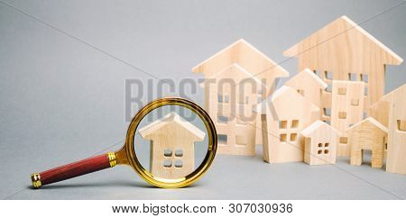 Magnifying glass and wooden houses. House searching concept. Home appraisal. Property valuation. Choice of location for the construction. Search for housing, apartments. Real estate appraiser services poster