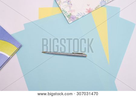 Ballpoint Pen Lies On Sheets Of Blue And Yellow Paper Next To The Notebook, White Background, Layout
