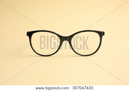 Modern Fashionable Acetate Spectacles, Black Color, Laying On Light Yellow Background.