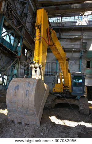 Crawler excavator for demolition work. Dismantling of an old industrial building. poster