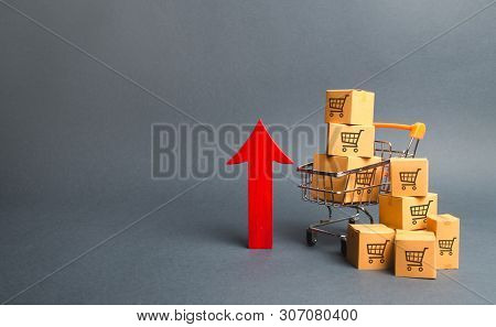 Shopping Cart With Cardboard Boxes With A Pattern Of Trading Carts And A Red Up Arrow. Growth Wholes