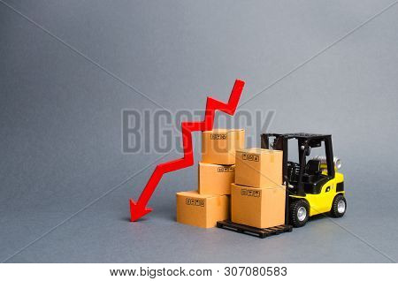 Yellow Forklift Truck With Cardboard Boxes And A Red Arrow Down. Concept Drop In Industrial Producti