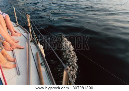 Many female legs on a white yacht. Feet over the water. Bachelorette party on the yacht, dissecting the waves. poster