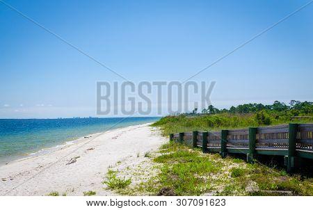 Ramp Walkway Leading To Inter-coastal Bay, Ocean Beach Shoreline With Waves Splashing Onshore. Pensa