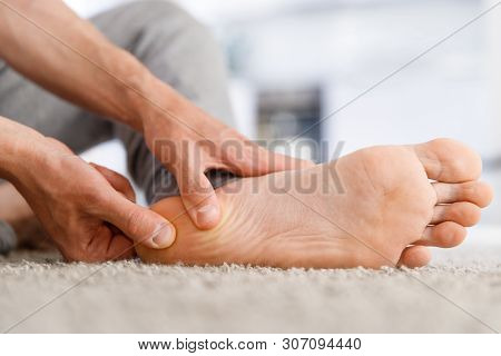 Man Hands Giving Foot Massage To Yourself After A Long Walk, Suffering From Pain In Heel Spur, Close
