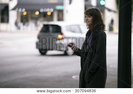 Female Pedestrian Waiting On A Sidewalk For A Rideshare.  She Is Sharing Her Gps Location Via Cellph