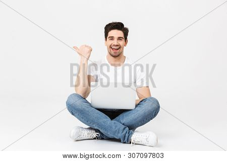 Image of happy excited young man posing isolated over white wall using laptop computer pointing sitting on floor.