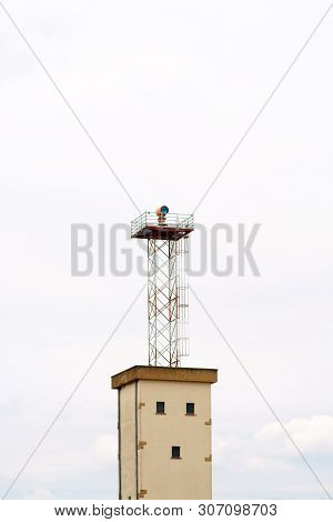 A Disused Watchtower With A Floodlight On A Disused Airport Area.