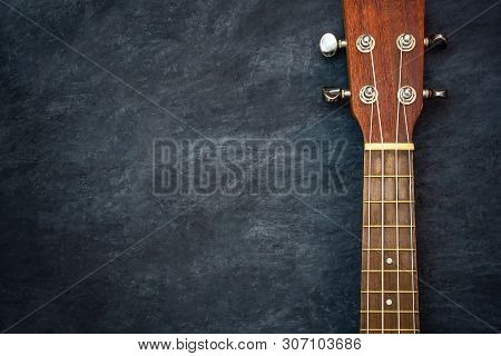 Ukulele On Black Cement Background. Headstock And Fret Of Ukulele Parts. Copy Space For Text. Concep