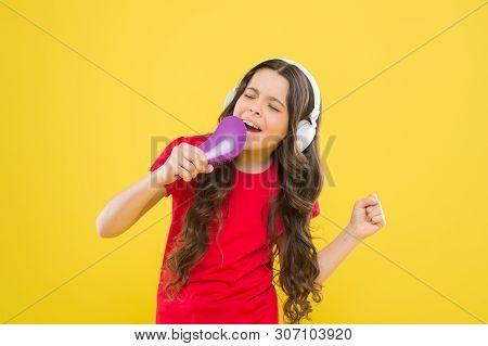 Karaoke star. Cute little girl pretending singing karaoke on yellow background. Adorable child performing karaoke song. Small singer performing karaoke soundtrack. poster