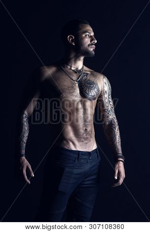 Bodycare with fitness and sport. Tattooed man show sexy muscular torso. Sportsman with six pack and ab. Bodybuilder with biceps and triceps. Fashion model with tattoo in jeans. poster