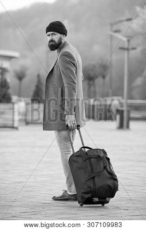poster of Carry travel bag. Man bearded hipster travel with luggage bag on wheels. Adjust living in new city. Traveler with suitcase arrive airport railway station urban background. Hipster ready enjoy travel.