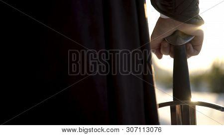 Man In Medieval Suit Holding Sword. Action. Close-up Of Man's Hand In Medieval Suit Holding Sword Hi