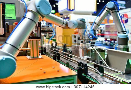 Robot Arm Arranged Glass Water Bottle On Automatic Industrial Machinery Equipment In Production Line