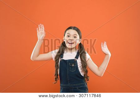 Looking Happy And Excited. Happy Little Girl With Cute Smile On Orange Background. Cheerful Small Ch