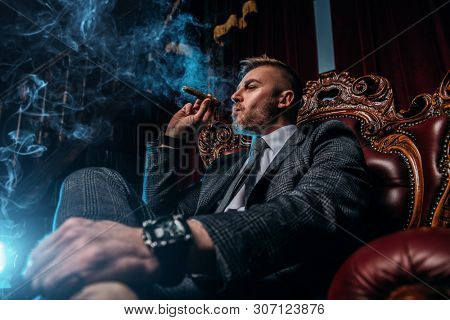 A portrait of a handsome mature man in a formal costume smoking a cigar in the interior. Men's beauty, fashion.