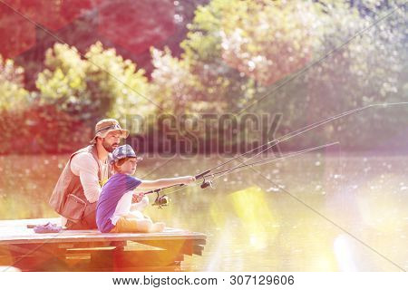 Father and son fishing in lake while sitting on pier