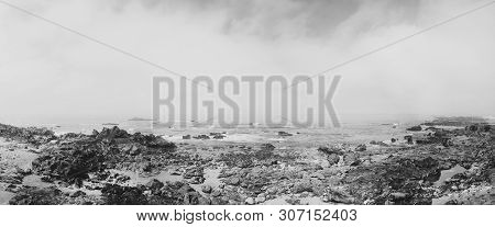 Rocky Shore With A Cloudy View Over Atlantic Sea In Portugal. Black And White Photo