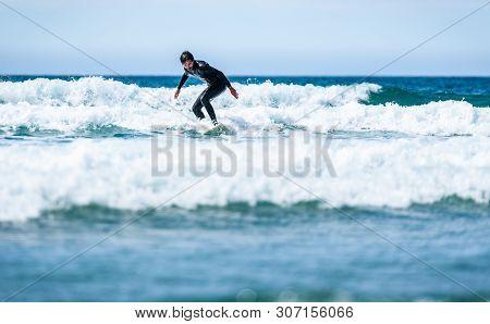 Surfer Guy Surfing With Surfboard On Waves In Atlantic Ocean.