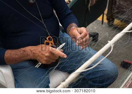 Old Fisherman Reparing Fishing Net Surfing The Day.