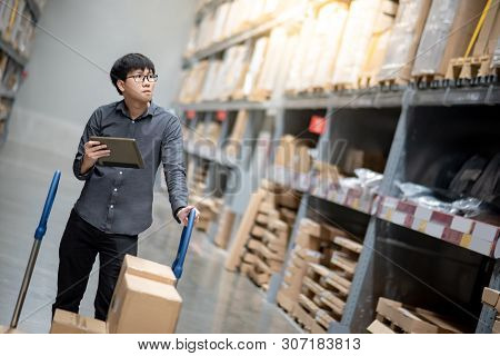 Young Asian Man Worker With Shopping Cart Doing Stocktaking Of Product In Cardboard Box On Shelves I