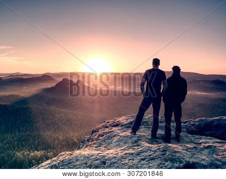 Boys Tourists Stay Together Close To Each Other On Summit. Dreamy Fogy Landscape Blue Misty Sunrise