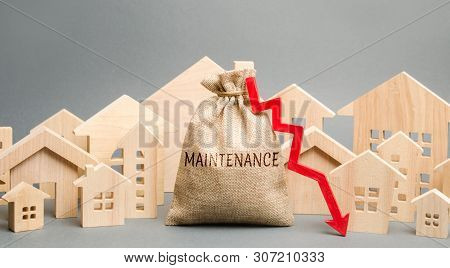 A Bag With The Word Maintenance, Wooden Houses And Down Arrow. Reducing The Cost Of Maintaining The