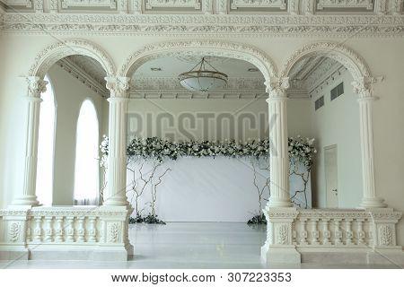 Indoor Wedding Light Photozone Decorated With Fresh Flowers.