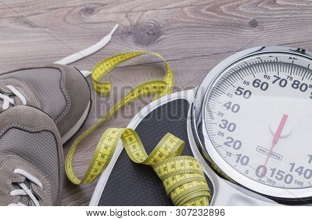 The Image Shows Running Shoes With Tape Measure And Weighing Scales On A Wooden Table