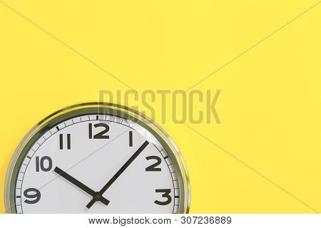 Part Of Analogue Plain Wall Clock On Trendy Yellow Background. Ten Oclock. Close Up With Copy Space,