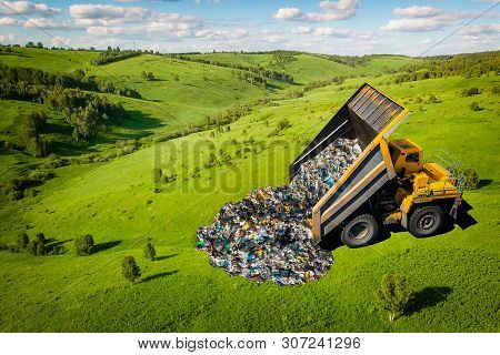 Garbage Truck Dumps Plastic Waste And Packages Onto Clean Green Field. Concept Pollution Of Environm