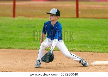 Youth Baseball Player In Blue Uniform Covering Second Base And Waiting For The Ball In The Infield D